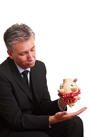 Elderly business man shaking an empty piggy bank photo