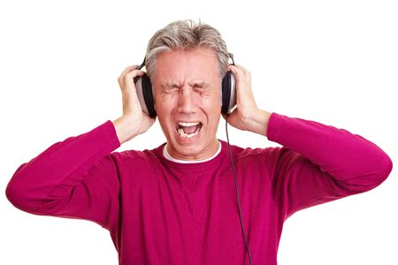 Senior man with headphones on screaming loudly photo