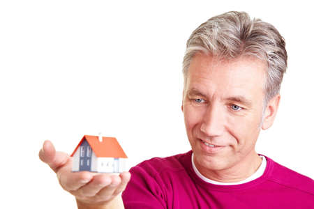Senior man looking at a small miniature house Stock Photo - 8903738