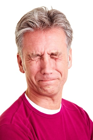 grimacing: Elderly man with grey hair grimacing with disgust