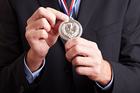 Hands in a business suit holding a silver medal photo