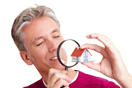Senior man looking at a small house with magnifying glass photo