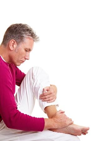 pies masculinos: Anciano masajear sus pies doloridos con sus manos