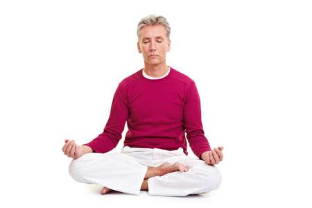 Senior man meditating in tailor seat on white photo