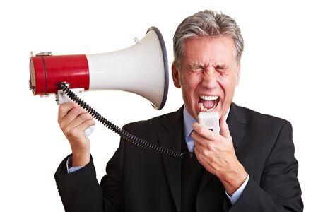 dolor de oido: Hombre de negocios mayores gritando ruidosamente en un meg�fono Foto de archivo