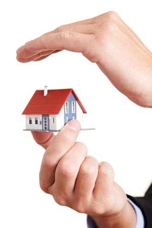 Hand protecting a small miniature house with a roof photo