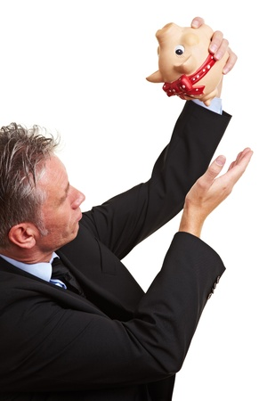 Senior business man holding his hand under an empty piggy bank photo