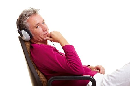 enjoy space: Relaxed senior man sitting on office chair and listening to music with headphones