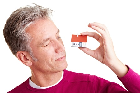 Senior man looking at a small miniature house Stock Photo - 8953293