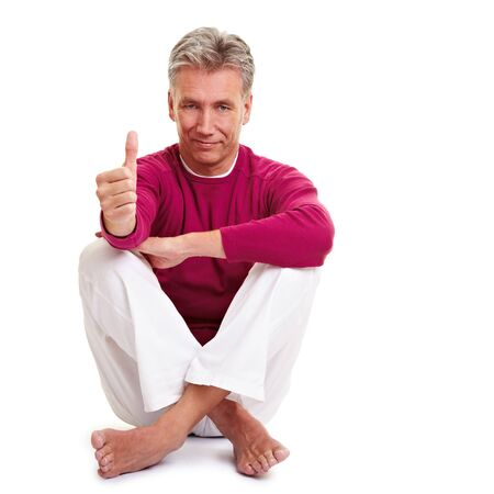 Relaxed yoga teacher holding his thumb up photo