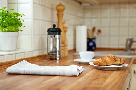 tabulka: Croissant and a cup of coffee on a kitchen counter