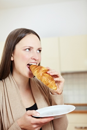 Beautiful pensive woman eating a croissant in a kitchen Stock Photo - 8988378