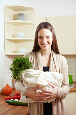 Attractive woman carrying shopping bag in kitchen Stock Photo - 8988370