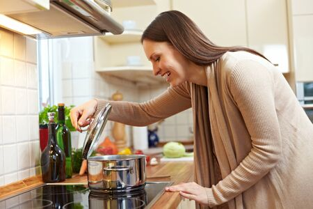 Woman in the kitchen watching food in a pot on the stove