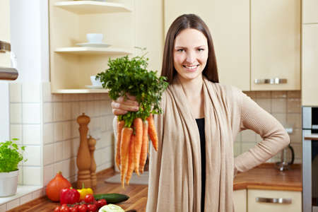 Happy woman holding bunch of carrots in the kitchen Stock Photo - 8988354