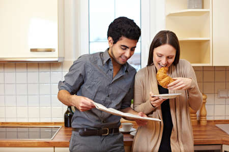 Happy couple having breakfast in the kitchen and reading newspaper Stock Photo - 8988356