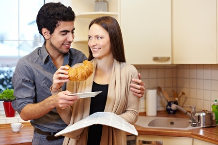 Happy couple in a kitchen sharing croissang and newspaper Stock Photo - 8988396