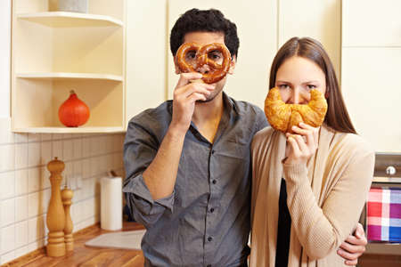 Couple in kitchen holding pretzel and croissant in front of their faces photo