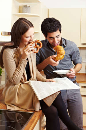 Couple having breakfast in the kitchen with pretzel and croissant Stock Photo - 8988392