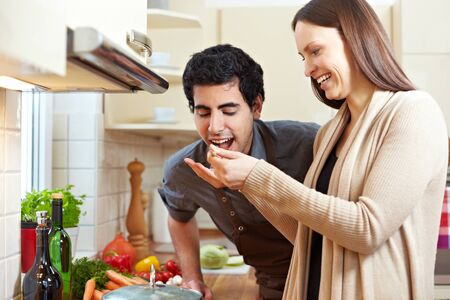 vegetables young couple: Smiling woman letting man taste a soup with a wooden spoon in the kitchen Stock Photo