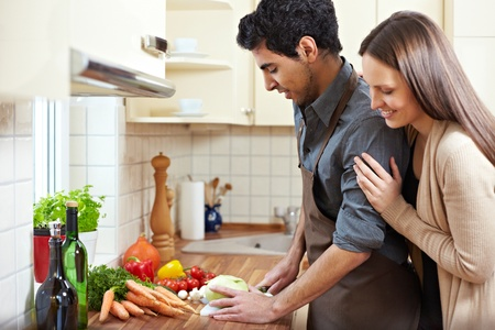 homemaker: Homemaker preparing lunch while happy woman is watching him Stock Photo