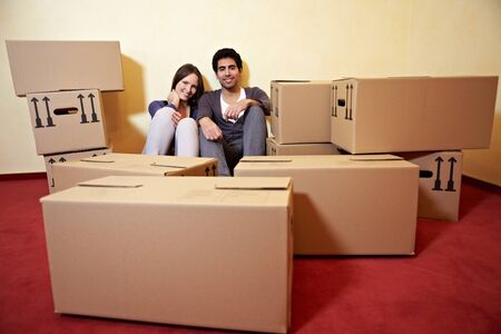 Happy couple sitting between many moving boxes in their new home photo