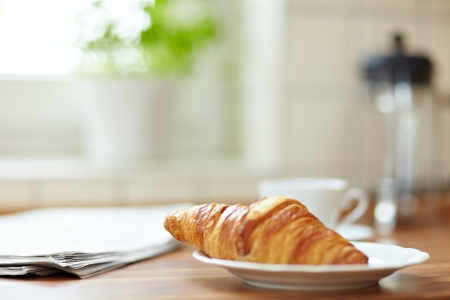 Croissant with newspaper and a cup of coffee on a kitchen counter Stok Fotoğraf - 8988435