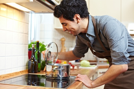 lids: Man watching a pot on a stove in the kitchen