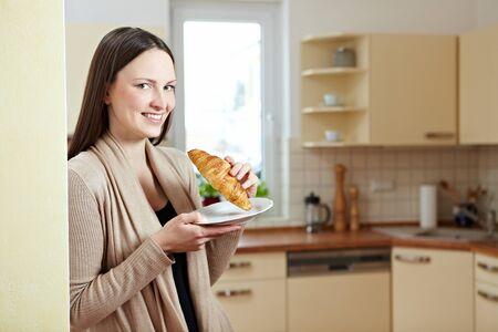 Attractive woman standing with croissant in a kitchen Stock Photo - 8988484