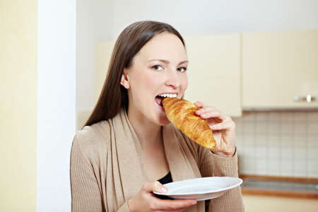 Happy woman biting in a croissant in a kitchen Stock Photo - 8988463
