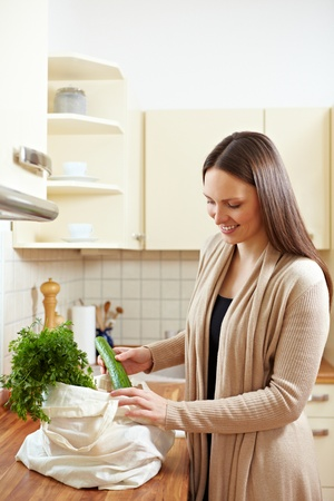 Happy woman unpacking groceries in the kitchen Stock Photo - 8988486