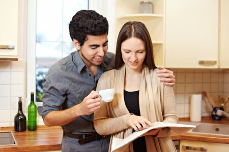 coffee houses: Young couple reading a newspaper together in the kitchen
