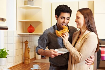 Woman in a kitchen sharing croissant with man photo