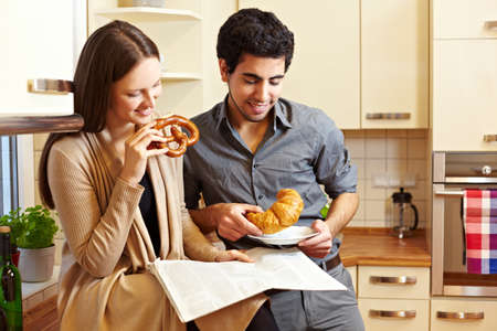 Couple having breakfast in the kitchen with pretzel and croissant Stock Photo - 8988503