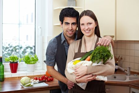 Happy couple with their groceries in the kitchen photo