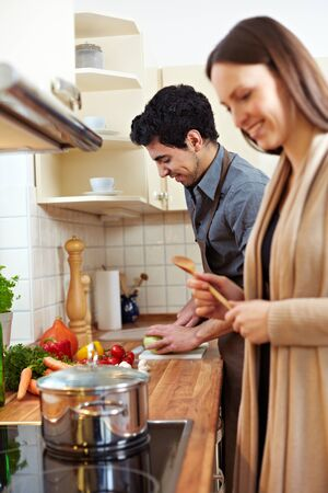 Happy young couple cooking a soup together in the kitchen photo