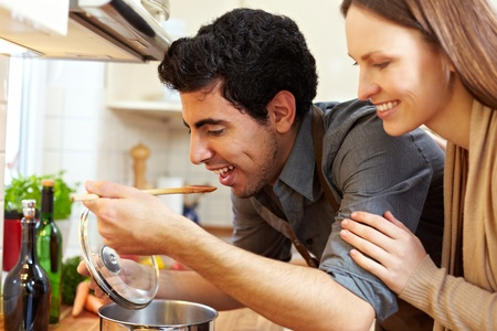 Man tasting soup on a stove in kitchen while happy woman is watching
