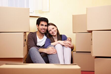Happy couple sitting between many packing cases in new appartment photo