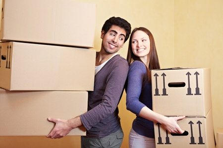 home moving: Couple in love carrying many moving boxes into their new home Stock Photo