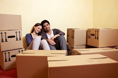 Tired couple sitting between many boxes in their new home photo