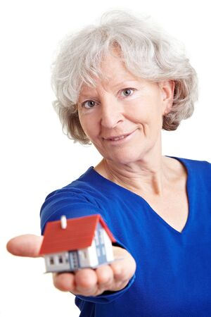 Happy senior woman holding small miniature house on her palm photo