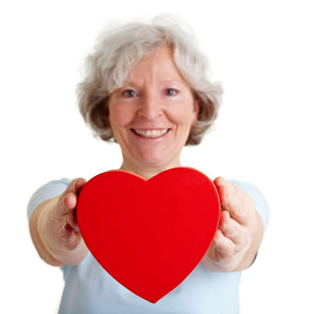 Smiling senior woman offering a red heart photo