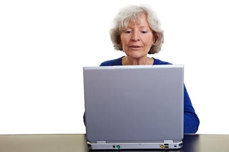 curso de capacitacion: Mujer senior feliz trabajando en un equipo port�til Foto de archivo