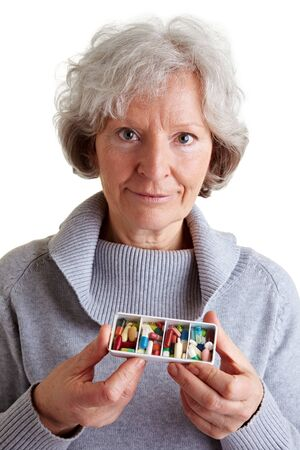 Old woman holding a filled pill dispenser photo