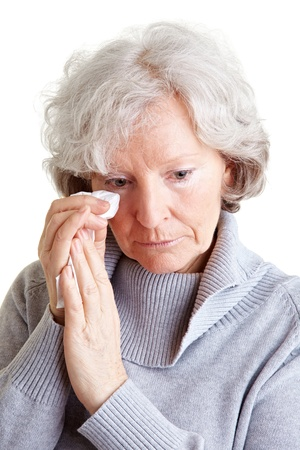 Old senior woman crying and drying her tears with a handkerchief photo