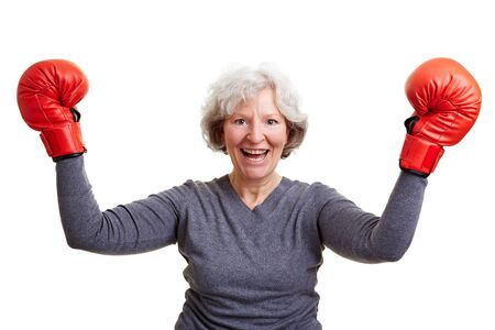 Happy senior woman cheering with red boxing gloves photo