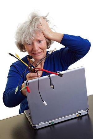 Gefrustreerde oude vrouw met laptop en veel verschillende computerkabels