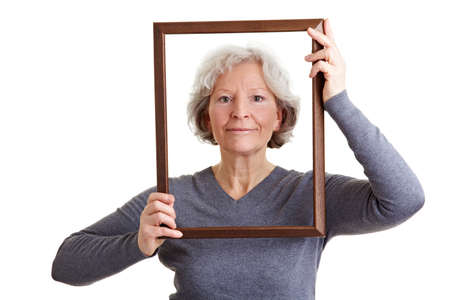 self conceit: Smiling old woman looking through an empty frame