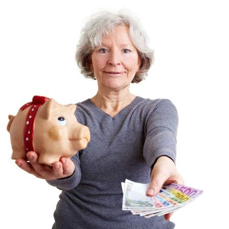 abastecimiento: Mujer senior con hucha ofreciendo dinero Euro Foto de archivo