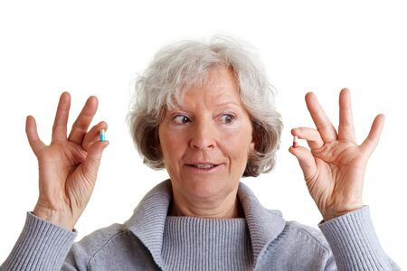 Sceptical old woman comparing two pills in her hands photo